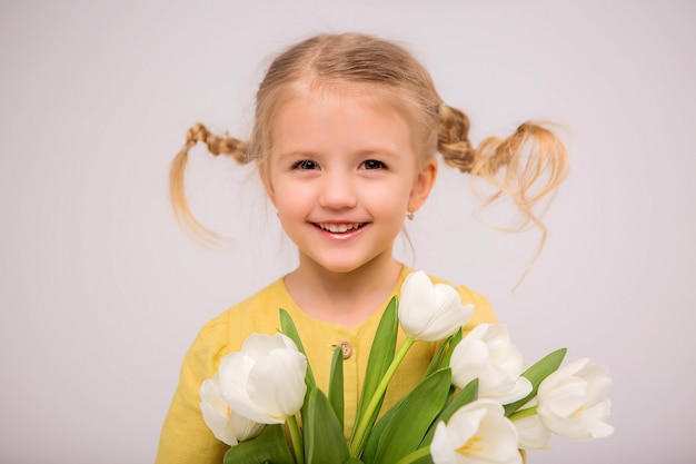 Baby girl blonde with a bouquet of tulips on a light background