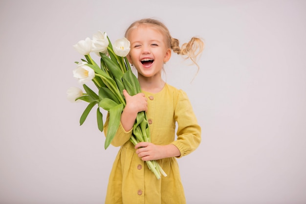 Baby girl blonde with a bouquet of tulips on a light background.