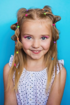 Baby girl on a blue background with bright elastic bands for hair