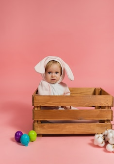Baby girl in a bunny costume sits in a wooden box with colorful eggs on a pink background.