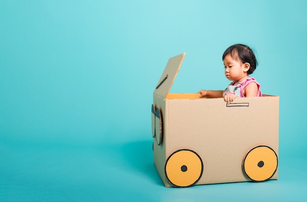 Baby girl in car made with cardboard box