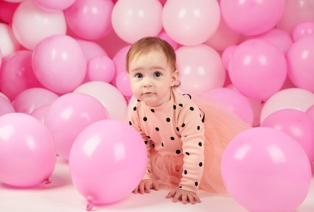 Baby girl celebrate her first birthday. girl on background of pink balloons. top view