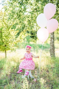 Baby girl celebrates her first birthday with cake and balloons in nature