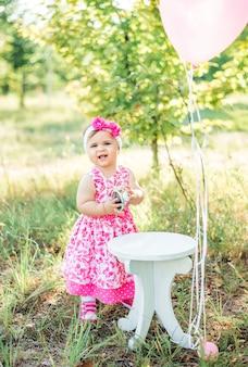 グルメケーキと風船で彼女の最初のbithdayを祝っている女の赤ちゃん。