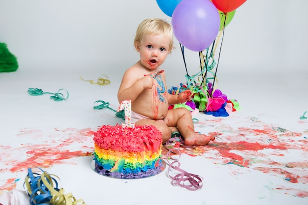 Baby girl celebrating her first bithday with gourmet cake and ba