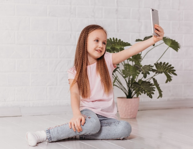 Baby girl chats on video on smartphone, takes selfie