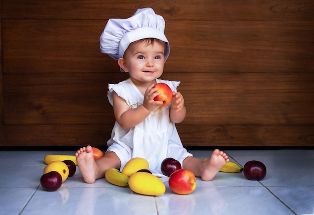 Baby girl in a chef's cap is sitting on the floor, holding an apple and smiling.