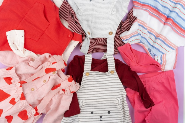 Baby girl clothes on lilac pastel surface
