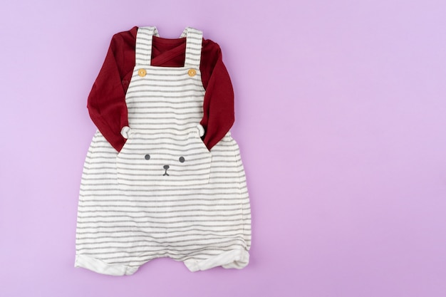 Baby girl clothes on lilac pastel