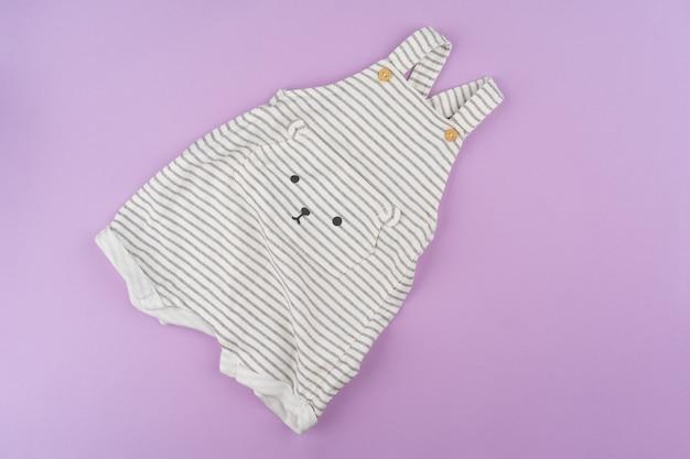 라일락 파스텔 배경에 아기 소녀 옷