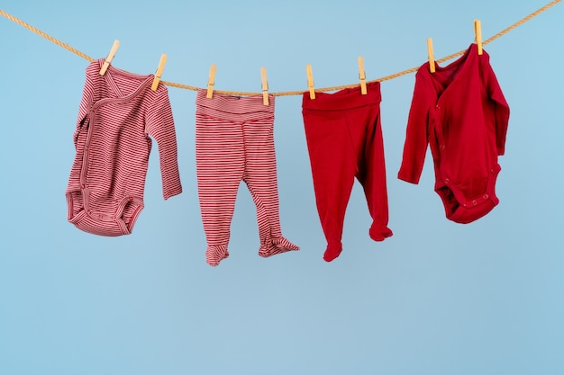 Baby girl clothes pinned on a clothesline against blue background