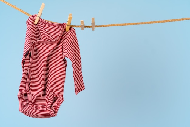 Baby girl clothes pinned on a clothesline against blue wall