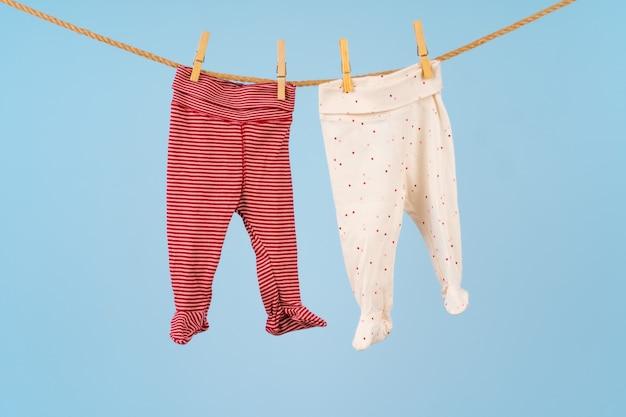 파란색 배경에 빨랫줄에 고정 된 아기 소녀 옷