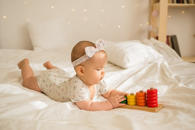 A baby girl in a colorful bodysuit and headband plays with an educational toy on white blanket on the bed. earlier development
