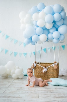 아기 소녀는 풍선 바구니에 바닥에 크롤링