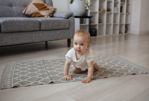A baby girl in a crimson jumpsuit crawls on a rug in the room