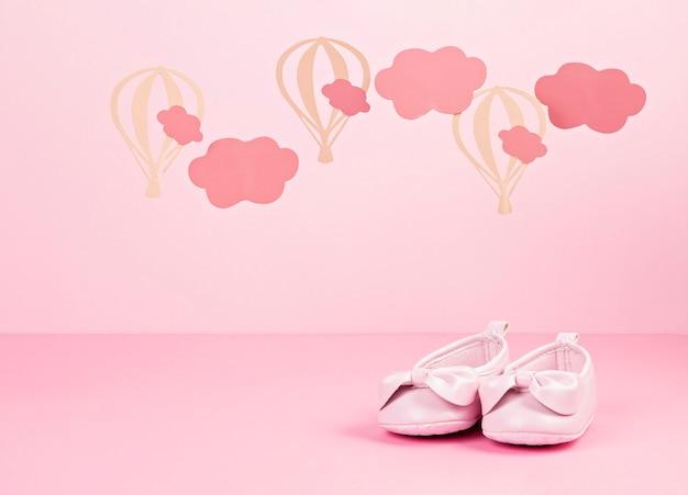 Детские милые розовые туфли на розовом пастельном фоне с облаками и шариками