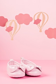 Baby girl cute pink shoes over the pink pastel background with clouds and ballons