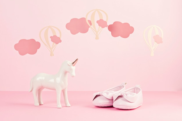 Baby girl cute pink shoes and unicorn over the pink pastel background