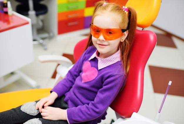 Baby girl in dental glasses smiling sitting in dental chair.