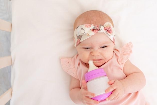 Девочка не хочет есть бутылку молока в кроватке, лежа на спине в детской, концепция детского питания