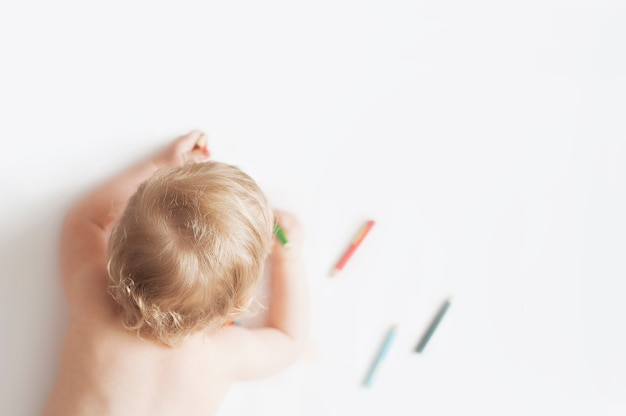 Baby girl drawing with colorful pencils on white background