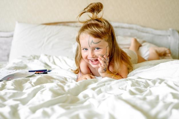 女の赤ちゃんはマーカーで手と足を描きます。子供たちはベッドで遊ぶ。家で朝。汚い子。