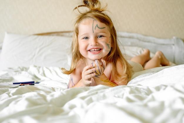 여자 아기는 마커 손과 발을 그립니다. 아이들은 침대에서 놀아요. 집에서 아침. 더러운 아이.