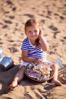 砂浜のビーチで船乗りに扮した女の赤ちゃん