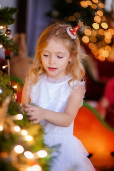 Baby girl dresses up a christmas tree