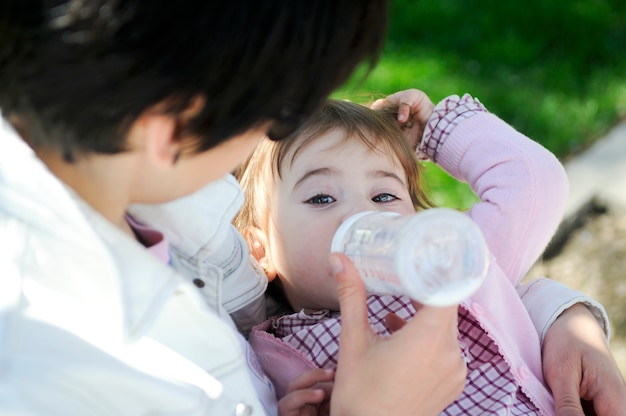 Baby girl drinking milk from baby bottle. mother feeding daughter from bottle.