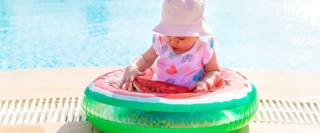 女の赤ちゃんはプールで膨らませてスイカでスイカを食べる