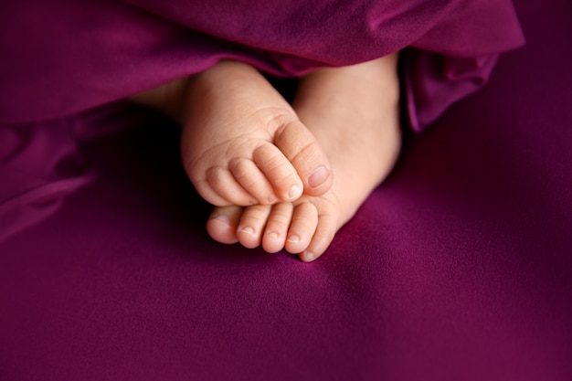 Baby girl feet on raspberry, closeup of barefeet, maternity and babyhood concept