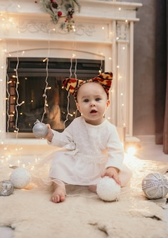 A baby girl in a fluffy dress and a headband with tiger ears sits near the fireplace in the room and plays with christmas balls