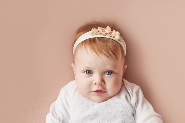 Baby girl of four months lies on a light pink wall