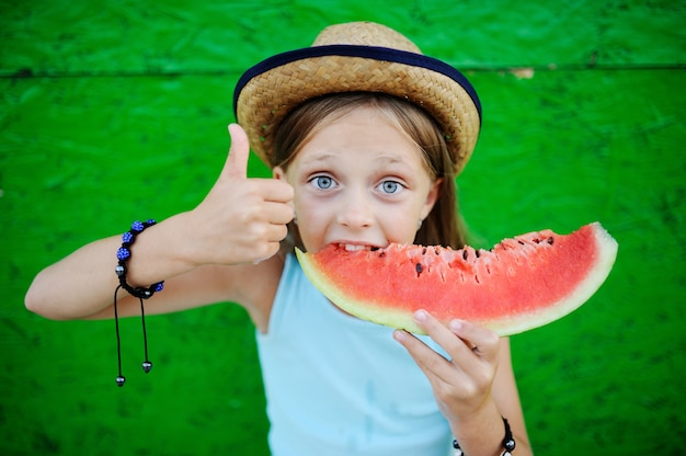 Baby girl greedily eating ripe watermelon on a green background