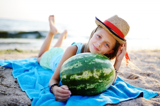 Baby girl in a hat with a large watermelon in his hands against the sea