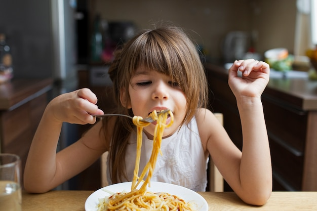 Baby girl having pasta dish indoor