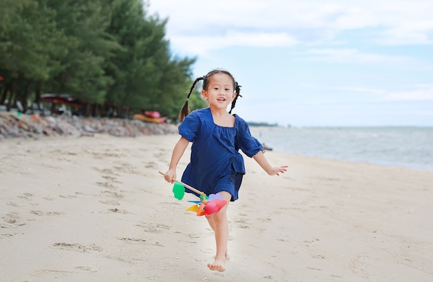 Baby girl hold colorful windmill toy and running on the beach