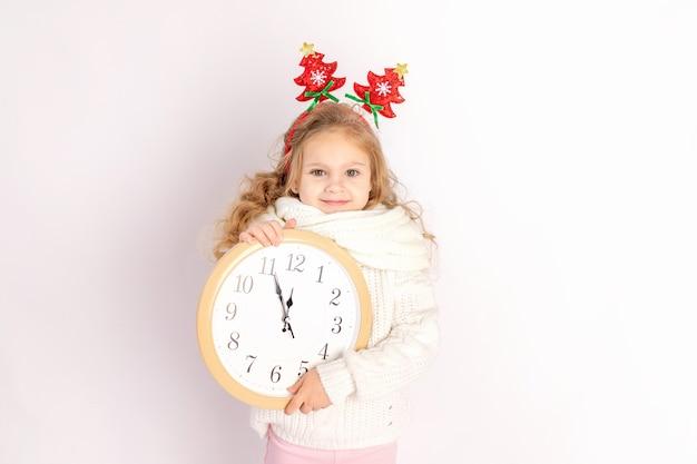 Девочка держит часы над белой