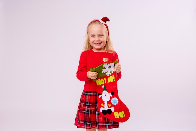 Baby girl holding christmas sock for gifts on white wall