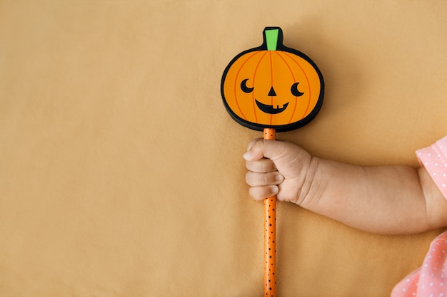 Baby girl holding stick with pumpkin on orange, copyspace on the left