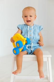 노란색 장난감 코끼리를 들고 아기 소녀입니다. 우는 유아. 감정적 인 한 살 어린이의 초상
