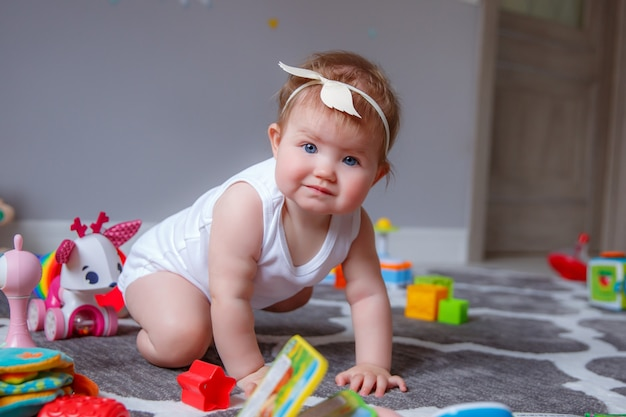 Baby girl at home sitting on the floor playing with toys