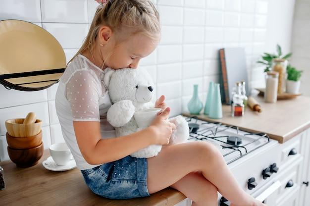 Baby girl hugs a teddy bear sitting in a beautiful stylish bright kitchen. teddy bear