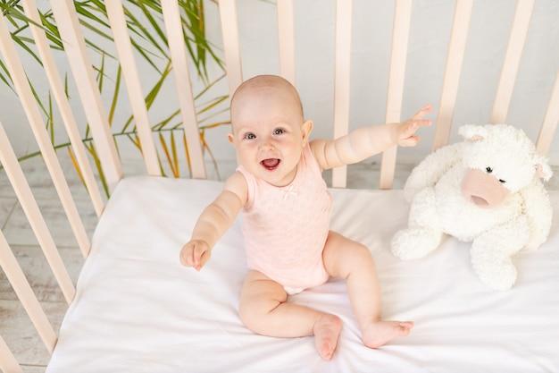 6개월 된 핑크색 바디수트와 테디베어를 입고 웃고 있는 아기 침대