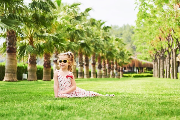 Девочка в парке возле деревьев.
