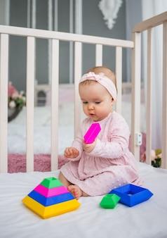 ピンクのドレスとヘッドバンドを着た女の赤ちゃんがベビーベッドに座って、カラフルなピラミッドを集めます。子供のためのパズルゲーム