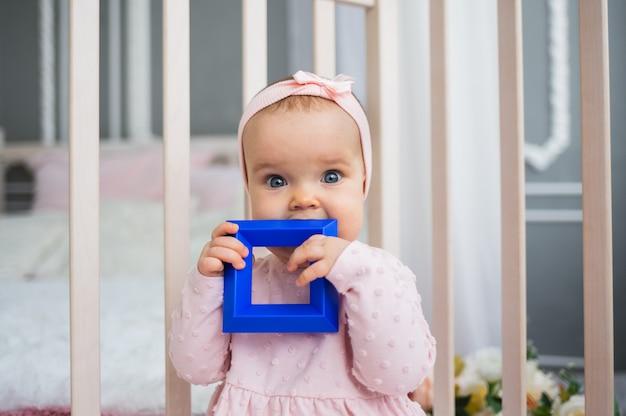 ピンクのドレスを着た女の赤ちゃんが座って、ベビーベッドでおもちゃをなめます。歯が生える