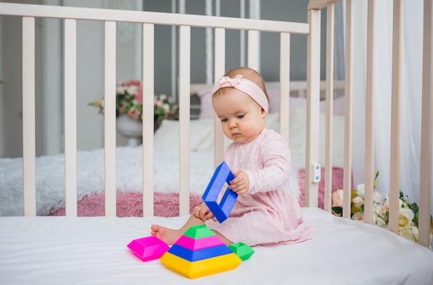 핑크 드레스에 아기 소녀는 침대에 앉아 다채로운 피라미드와 함께 재생